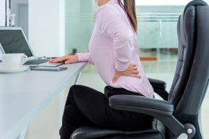 Picture of woman at desk with lower back pain